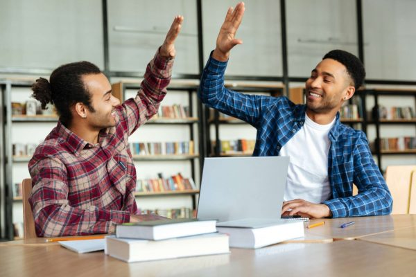 Two mixed race male students giving high five while studying with laptop at the library